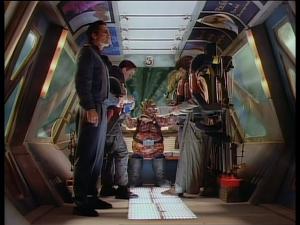 Jetzt nehmen uns die Aliens schon unsere Haltebügel weg! Weil Cephir Groxebul vom Planeten Lazando gern auf großem Fuß lebt, muss Commander NichtSheridan mit einem Stehplatz Vorlieb nehmen. Glücklicherweise spielt er so steif, dass er eins wird mit der Haltestangen